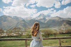 Холмы дома платья одного девушки смотря горы идут снег Стоковое фото RF