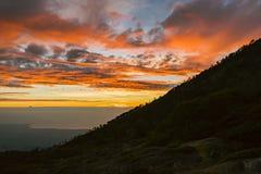 Холмы с красивым оранжевым небом с облаком стоковое фото rf