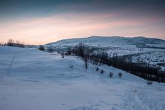 Холм Snowy на красочном заходе солнца стоковое изображение rf