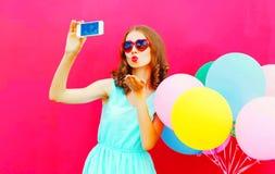 Холодная девушка фотографируя на smartphone посылает поцелуй воздуха Стоковое фото RF