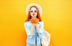 Холодная молодая женщина девушки посылает поцелуй воздуха на оранжевой предпосылке стоковое фото rf