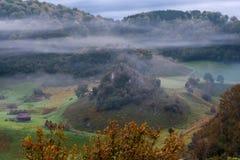 Холодное туманное утро в сногсшибательном дистанционном размещении, деревня Fundatura Ponorului, Румыния стоковые изображения rf