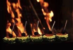 Холодные закуски, канапе с красной икрой, огнем на предпосылке Канапе с оливками, красной икрой, лимоном и укропом вкусно Стоковые Фото
