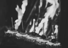 Холодные закуски, канапе с красной икрой, огнем на предпосылке Очень вкусные закуски служили в ресторане на черных блюдах Стоковые Фото