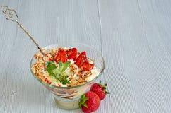 Холодный десерт с отрезанными клубниками, взбитая сливк лета в стеклянном шаре на серой предпосылке кухни с космосом экземпляра Стоковое Изображение