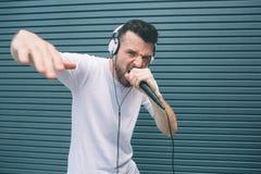 Холодный и внушительный человек читает рэп в микрофоне Он показывает его руку и смотрит камеру Гай поет в mic стоковое изображение rf