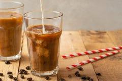 Холодный кофе лить в сливк, молоке в прозрачных стеклах с льдом и соломах, на деревянной предпосылке, охлаждая напиток, освежая стоковые фотографии rf