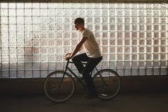 Холодный мальчик ехать классический велосипед и смотря прямо Молодой человек в белой футболке освобождая велосипед с стеклянной с Стоковые Фото