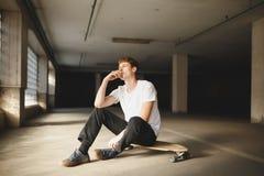Холодный мальчик при коричневые волосы сидя на скейтборде и курить Молодой заботливый человек в белых усаживании и удерживании фу стоковая фотография rf