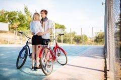 Холодный мальчик при светлые волосы стоя милая девушка и обнимая ее в парке Молодые пары стоя и смотря на одине другого Стоковое фото RF