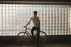 Холодный мальчик стоя с классическим велосипедом и dreamily смотря в сторону представляющ на камере Молодой заботливый человек в  Стоковые Изображения RF