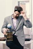 Холодный парень носит серый костюм Концепция дела и знания Бизнесмен с кучей старых книг Стоковое фото RF
