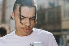 Холодный парень отправляя СМС на его телефоне стоковая фотография