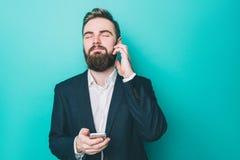 Холодный парень стоящ и слушающ к музыке на телефоне Он использует наушники для того Человек наслаждается моментом Стоковые Фотографии RF