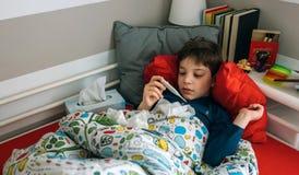 Холодный ребенок смотря термометр стоковое изображение rf