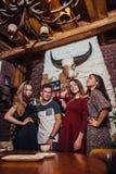 4 холодных подростка нося вскользь одежды представляя для камеры в стильном с дизайном интерьера охотничьего домика Стоковые Изображения