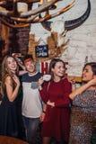 4 холодных подростка нося вскользь одежды представляя для камеры в стильном с дизайном интерьера охотничьего домика стоковое изображение