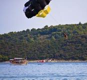 Хорватия, остров Ciovo - 2 девушки и мальчик наслаждаясь морем парашютируют Стоковые Изображения