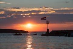 Хорватский полет при ветре флага на заходе солнца в гавани стоковая фотография