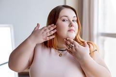 Хорошая выглядя пухлая женщина касаясь ее щеке стоковые изображения rf