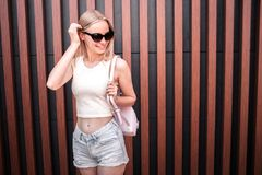 Хорошая и уверенно модель стоит и представляет Она держит портмоне на ее плече и смотрит к праву alric стоковые изображения