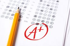 Хорошая ранг положительной величины написана с красной ручкой на тестах стоковое фото rf