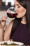 Хорошее вино. Портрет красивых зрелых женщин выпивая вино в r Стоковые Фото