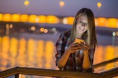 хорошие новости Отправка СМС молодой счастливой женщины усмехаясь на ее телефоне Стоковая Фотография