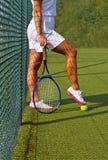 Хорошие ноги спорт стоят с ракеткой на суде на солнечном летнем дне Стоковое Фото