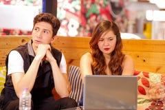Хорошие смотря пары на баре тратя время совместно, человек представляя обе руки под его щеками пока женщина работает внутри Стоковые Фото