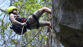Хороший выглядя азиатский парень rappelling от скалы на джунглях Весьма опасный акции видеоматериалы