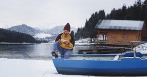 Хороший выглядя молодой туристский человек имеет период отдыха он сидя на голубой шлюпке рядом с озера берега и смотря до конца видеоматериал