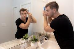 Хороший выглядя молодой человек расчесывая и смотря его волосы, бороду, и сторону в его домашнем зеркале Bathroom в утре получая  стоковое изображение rf