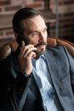 Хороший смотря бородатый бизнесмен связывая через сотовый телефон Стоковые Изображения RF