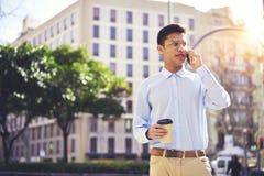 Хороший смотря парень битника смотря отсутствующий и имея переговор через мобильный телефон Стоковое Фото