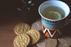 Хороший чай с травами и печеньями в кухне Стоковые Изображения RF