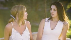 2 хороших друз имеют сердце к переговору сердца вне на скамейке в парке Девушки нося платья белизны обсуждают акции видеоматериалы
