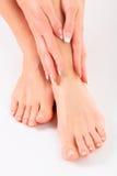 Хорошо выхоленные руки на женских ногах Стоковые Фотографии RF