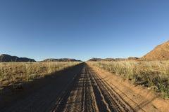 Хорошо используемая, пылевоздушная дорога пустыни к нигде Южная Намибия Окружать пейзажа горы стоковые фото