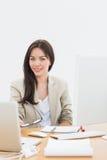 Хорошо одетая женщина с компьтер-книжкой на столе в офисе Стоковое фото RF