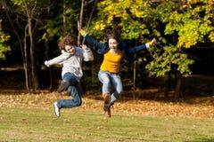 Ход девушки и мальчика, скача в парк Стоковое Фото