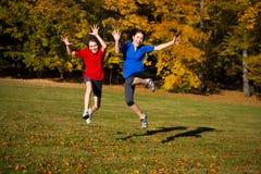 Ход девушки и мальчика, скача в парк Стоковая Фотография RF