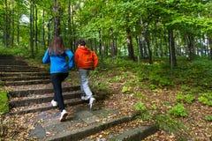 Ход девушки и мальчика, скача в парк Стоковые Фото