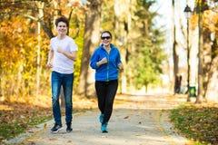 Ход девушки и мальчика, скача в парк Стоковое Изображение