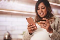 Ходить по магазинам беременной женщины онлайн с кредитной карточкой и мобильным телефоном Стоковое Фото