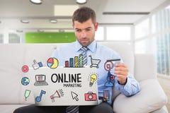 Ходить по магазинам бизнесмена онлайн пока сидящ на софе с онлайн текстом маркетинга в переднем плане Стоковая Фотография