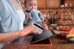 Ходить по магазинам женщины и ребёнка онлайн с цифровыми таблеткой и кредитной карточкой Стоковое Изображение RF
