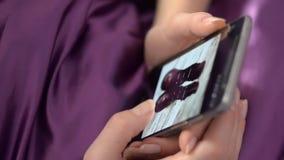 Ходить по магазинам женщины онлайн используя Smartphone, лежа в кровати акции видеоматериалы