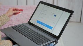 Ходить по магазинам женщины онлайн на компьтер-книжке с кредитной карточкой Стоковое Фото