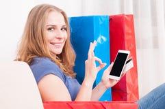 Ходить по магазинам женщины онлайн на smartphone делая одобренный жест Стоковое фото RF
